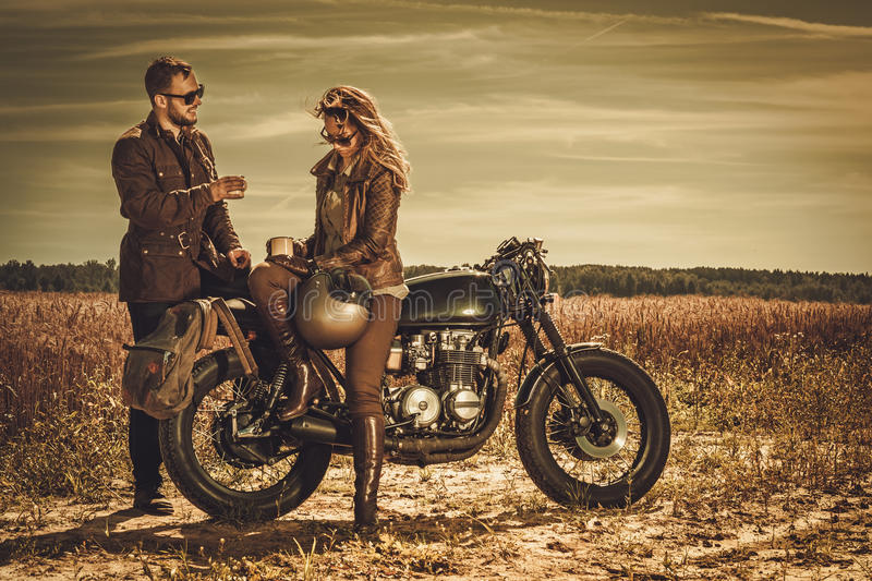 Stylish cafe racer couple on the vintage custom motorcycles in a field. Young, stylish cafe racer couple on the vintage custom motorcycles in a field stock images