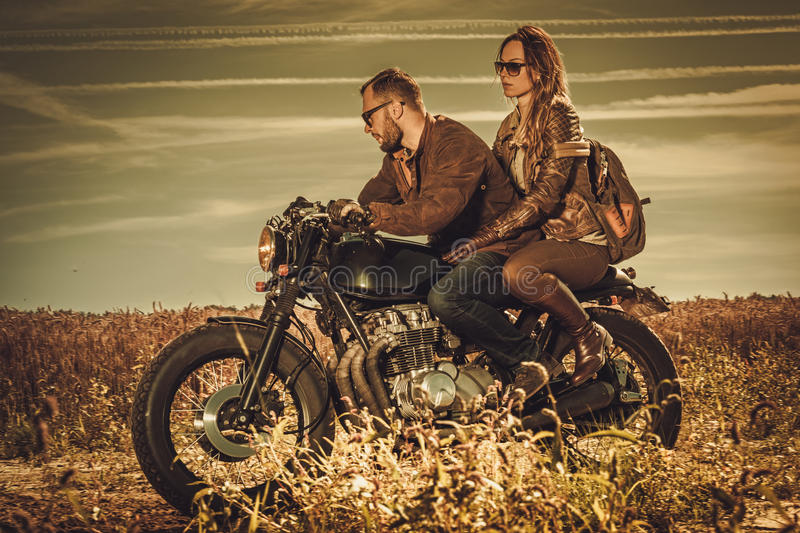 Stylish cafe racer couple on the vintage custom motorcycles in a field. Young, stylish cafe racer couple on the vintage custom motorcycles in a field royalty free stock photography