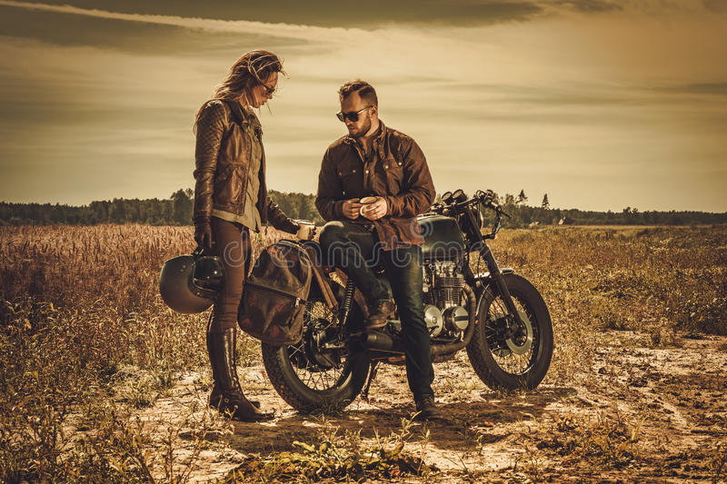 Stylish cafe racer couple on the vintage custom motorcycles in a field. Young, stylish cafe racer couple on the vintage custom motorcycles in a field royalty free stock photos