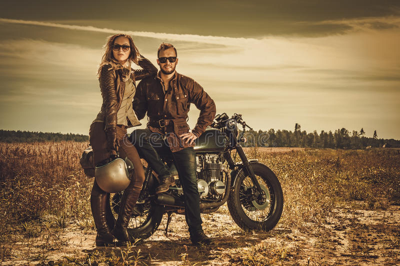 Stylish cafe racer couple on the vintage custom motorcycles in a field. Young, stylish cafe racer couple on the vintage custom motorcycles in a field stock photography