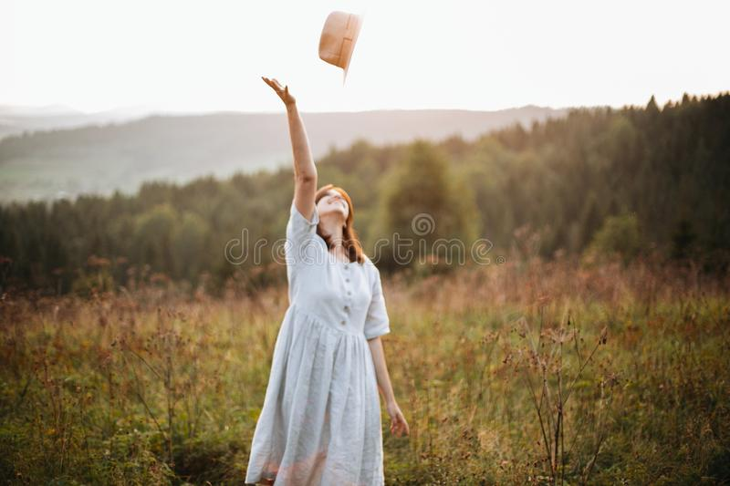 Stylish carefree boho girl throwing her hat in the sky in sunny light  at atmospheric sunset. Happy hipster woman in linen rustic. Dress enjoying traveling in royalty free stock image