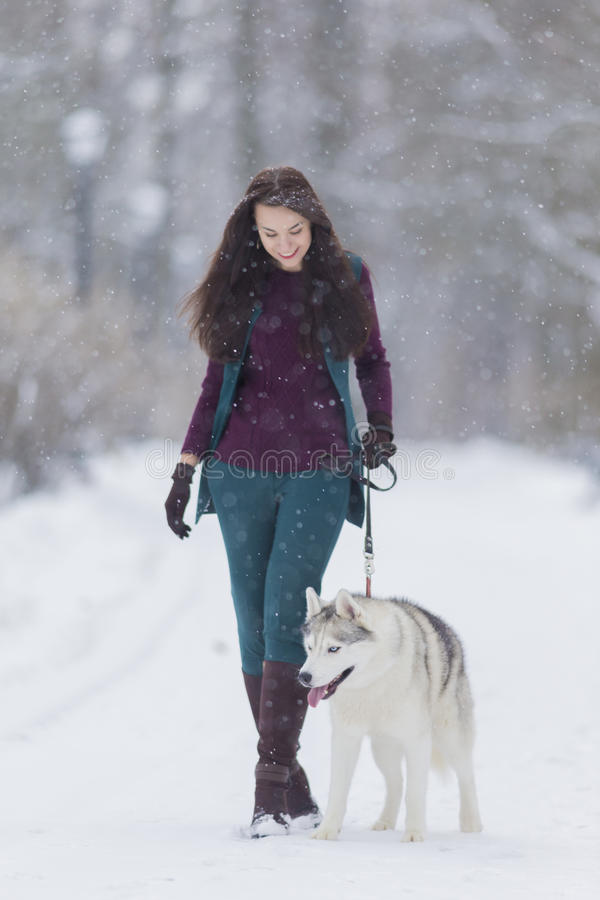 Stylish Caucasian Brunette Woman in Country Style Airing Her Husky Dog in Winter Snowy Forest. Outside.Vertical Image stock images