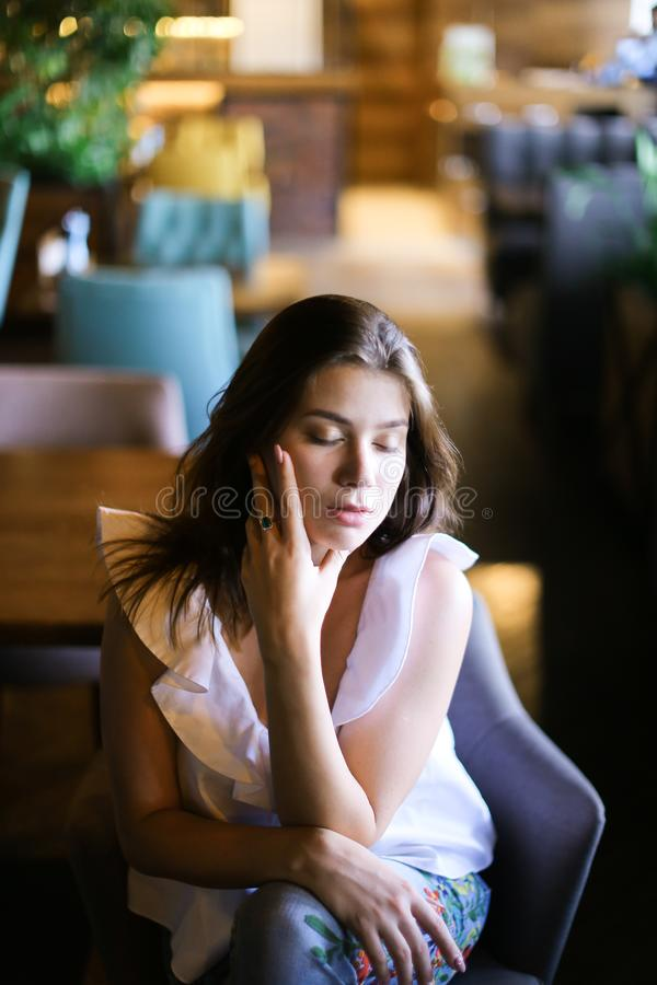 Stylish caucasian photo model sitting at cafe and wearing white blouse with ethnic jeans. stock image