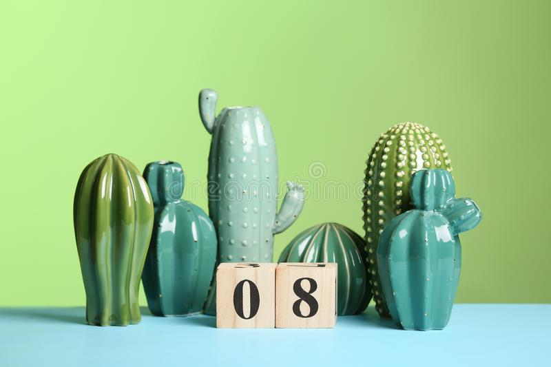 Stylish ceramic cactuses and wooden block calendar on table against color background. royalty free stock photography