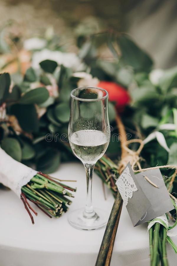 Stylish champagne drink on wedding table at green bouquets. luxury glass of champagne for celebration, reception outdoors. Catering royalty free stock images