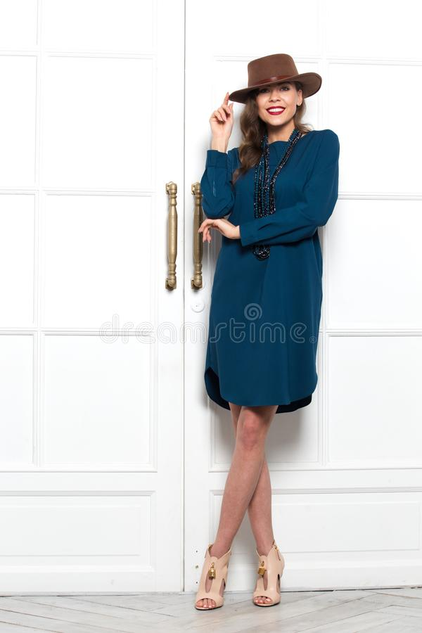 Stylish charming girl dressed in a fashionable emerald dress poses against a white wall in the room royalty free stock image