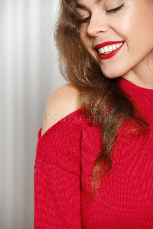 Stylish charming girl with red lipstick dressed in a red sweater poses poses against a white wall in the room royalty free stock photos