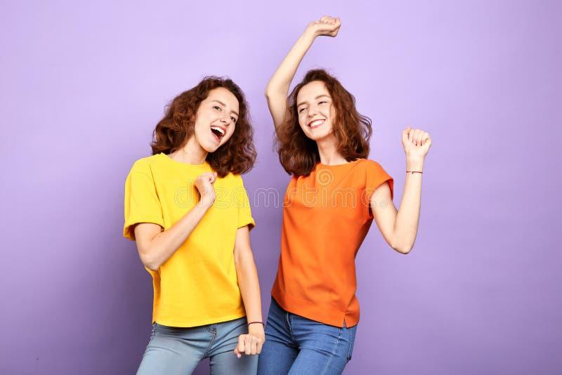 Stylish cheerful beautiful two sisters having fun in the studio with blue wall stock photo