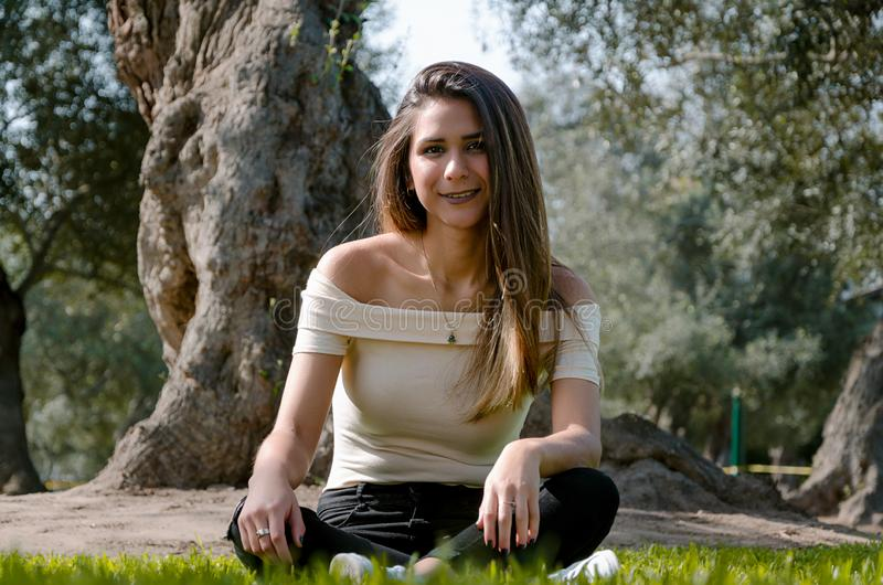 Stylish cheerful brunette sitting under a tree in a park stock image