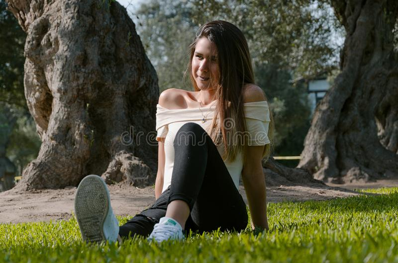 Stylish cheerful brunette sitting under a tree in a park stock photo