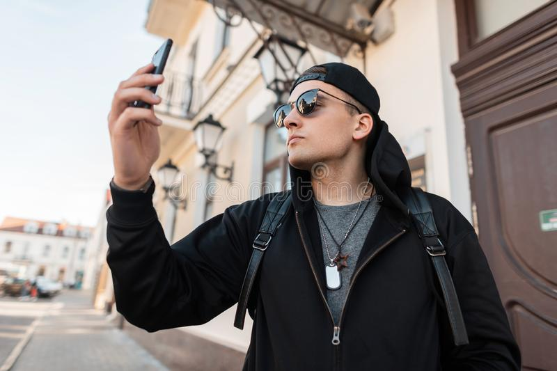 Stylish cheerful young man in a black sweatshirt with a hood in stylish sunglasses in a trendy cap is smiling and making a selfie royalty free stock image