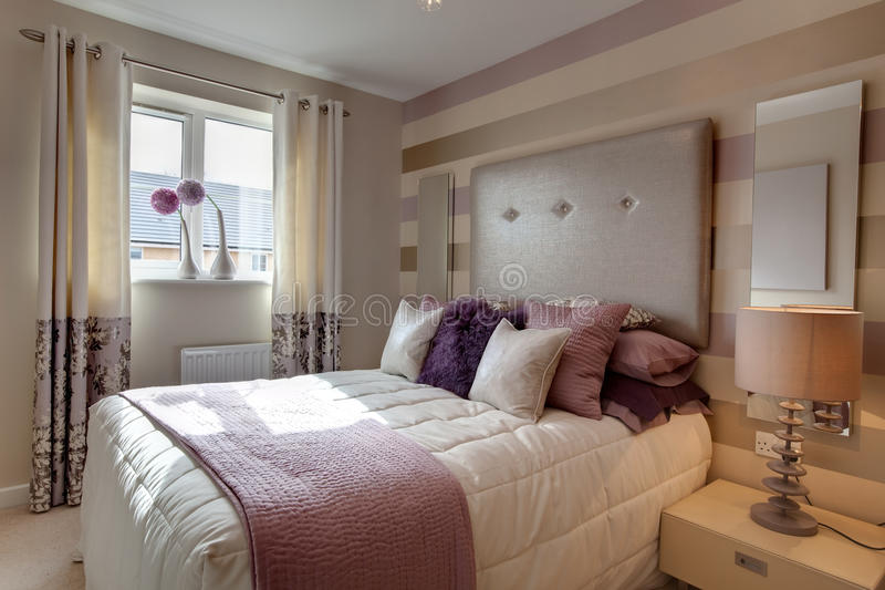 Stylish chic modern bedroom. Opulent modern bedroom with fashionable oversized headboard and brightly colored fabrics royalty free stock photos