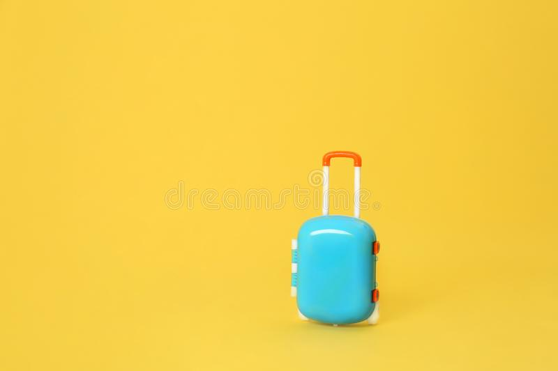 Stylish child blue suitcase on yellow background. Space for text royalty free stock image