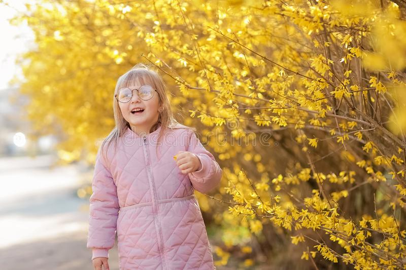 Stylish child girl 5-6 year old wearing trendy pink coat in autumn park. Looking at camera. Autumn season. Childhood stock photo