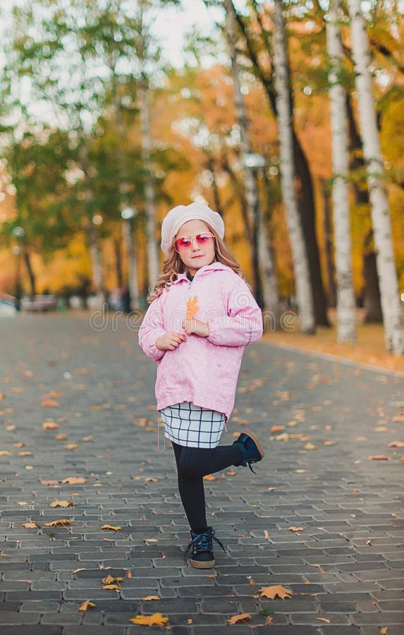 Stylish child girl 5-6 year old wearing trendy pink coat in autumn park. Looking at camera. Autumn season. Childhood. stock image