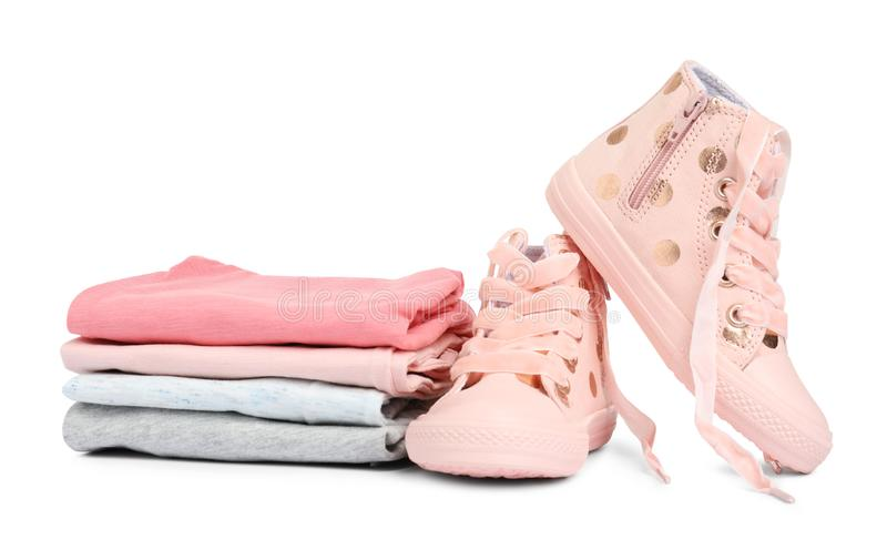 Stylish child shoes and stack of clothes. On white background stock photography