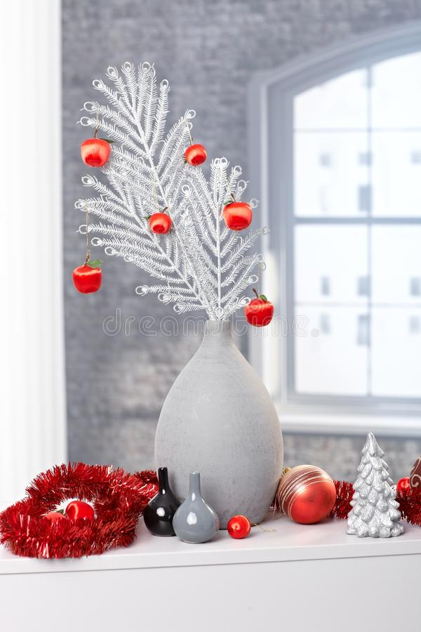 Stylish christmas decoration. Silver vase with white tree branch, red bulb and garland royalty free stock images
