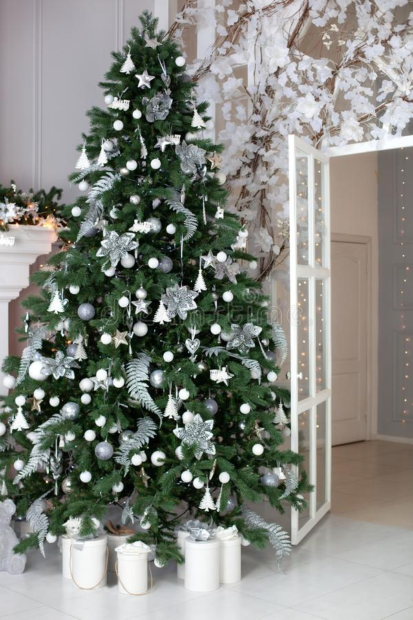 Stylish Christmas living room interior - bright room with Christmas - tree decorations - Christmas trees, gifts at the beautiful g. Lass door of house.  Festive stock photos