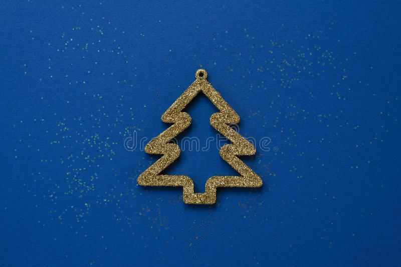 Stylish Christmas or new year greeting card. Christmas toy Golden Christmas tree on a blue background. With sequins royalty free stock photos
