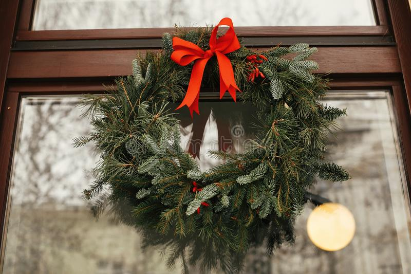 Stylish christmas wreath with red bow and berries at front of store at holiday market in city street. Space for text. Rustic royalty free stock image