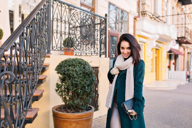 Stylish city young woman walking on street in green coat and white knitted scarf. Fashionable model with cut brunette royalty free stock photography