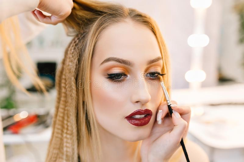 Stylish closeup portrait of gorgeous young woman in hairdresser salon preparing to party. Making hairstyle, makeup stock photography