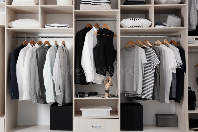 Stylish clothes and home stuff in large closet. Stylish clothes and home stuff in large wardrobe closet royalty free stock photo