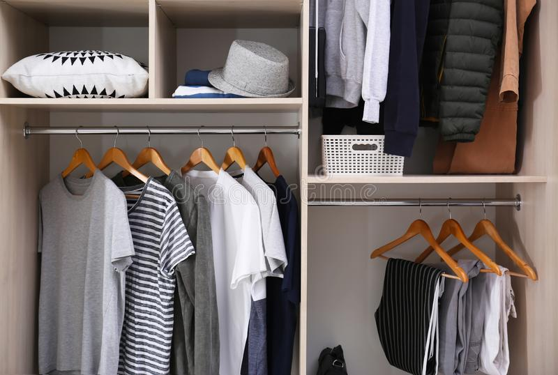 Stylish clothes and home stuff. In large wardrobe closet stock image