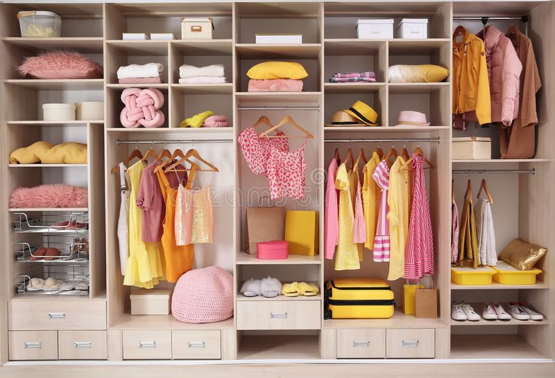 Stylish clothes, shoes and accessories in large closet stock image