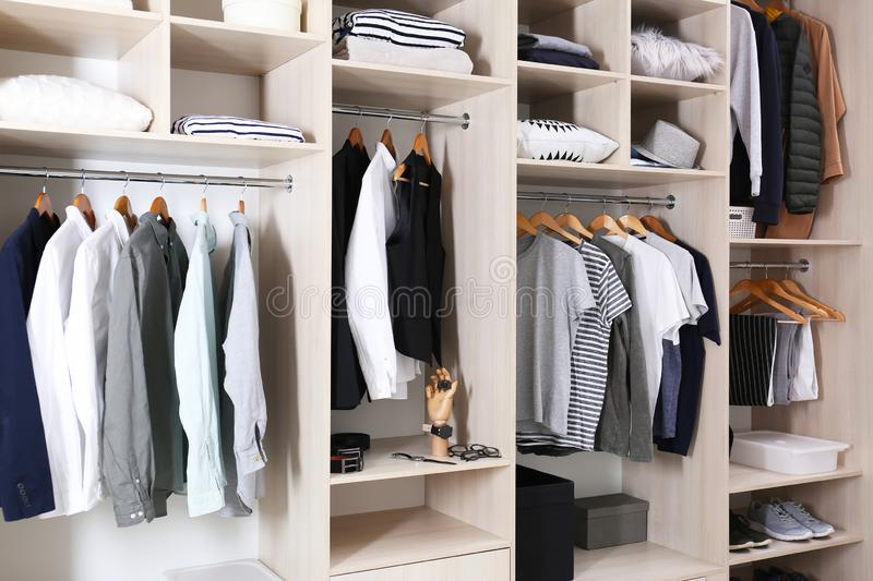 Stylish clothes, shoes and home stuff. In large wardrobe closet stock photography