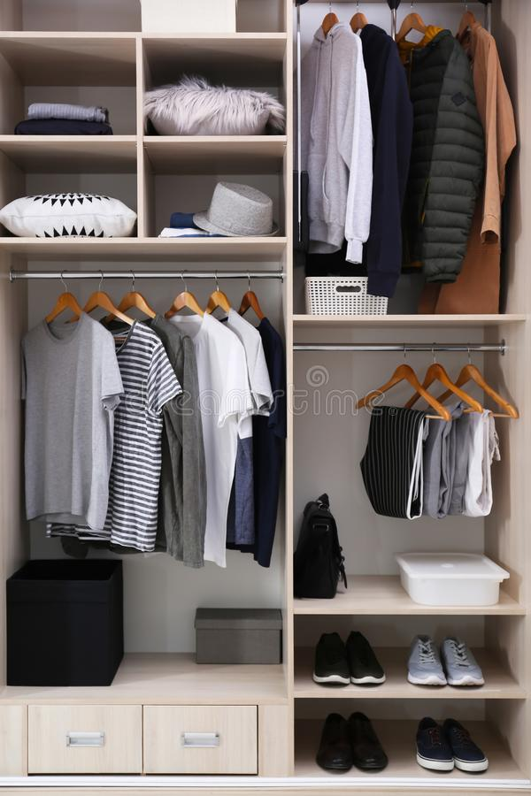 Stylish clothes, shoes and home stuff in large wardrobe. Closet royalty free stock images