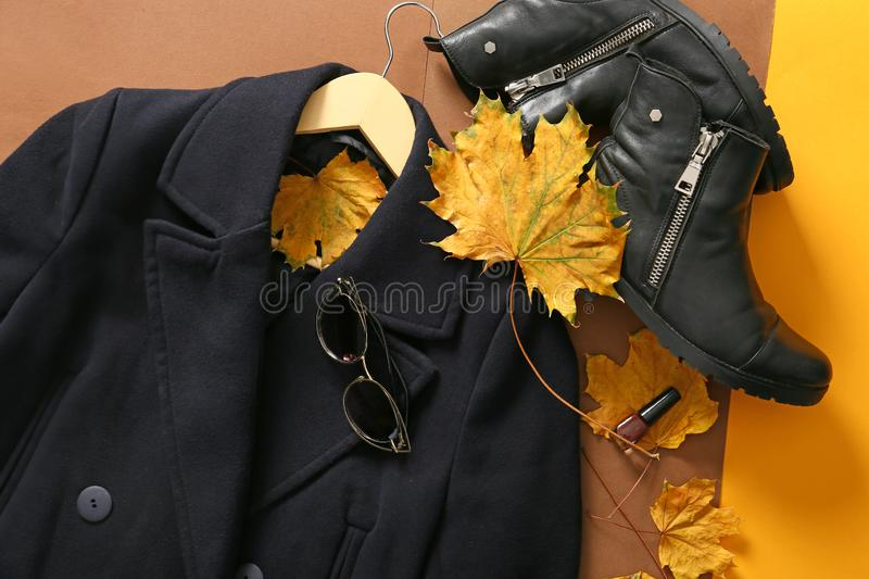 Stylish coat with boots and autumn leaves on color background, top view stock photo