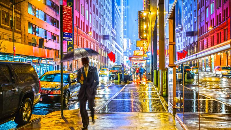 Stylish colorful wet New York NYC commuter with umbrella. Stylish colorful wet New York street photography image of a commuter with umbrella stock photos