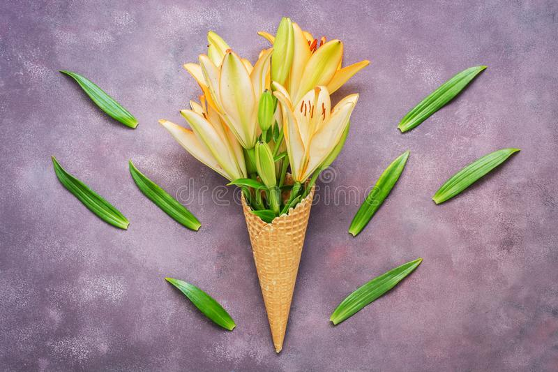 Stylish composition of yellow lily flowers in a waffle cone, scattered green leaves on a rustic purple background.Flat lay , copy stock photo