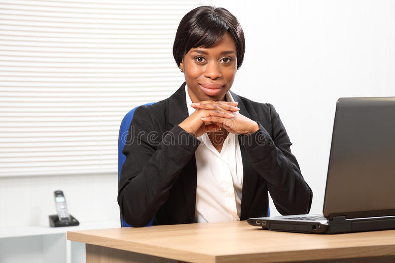 Stylish confident beautiful black business woman. Confident looking young black business woman in office sitting to her desk resting her chin on folded hands royalty free stock photography