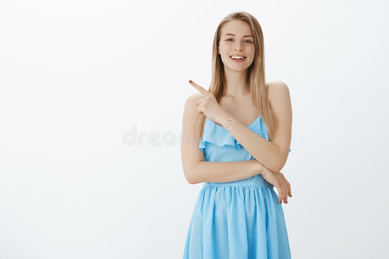 Stylish and confident good-looking woman with fair hair in elegant blue dress asking question as seing interesting thing. Pointing left and smiling friendly at stock image