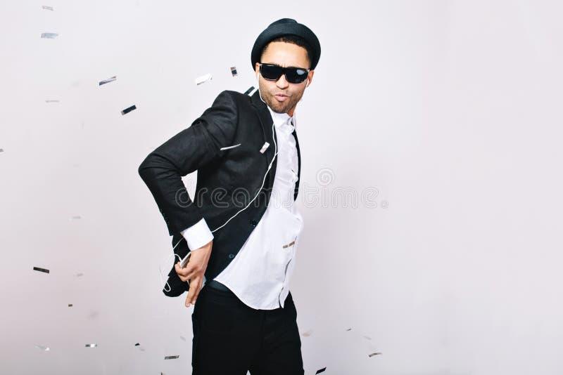 Stylish cool joyful guy in suit, hat having fun in tinsels on white background. Leisure, cheerful mood, joy, listening stock image