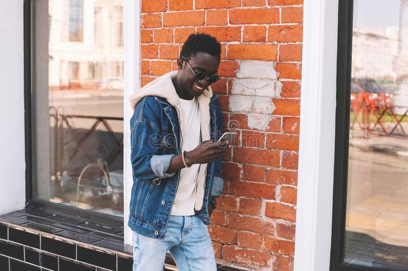 Stylish cool smiling african man with smartphone on city street over brick wall. Background royalty free stock image