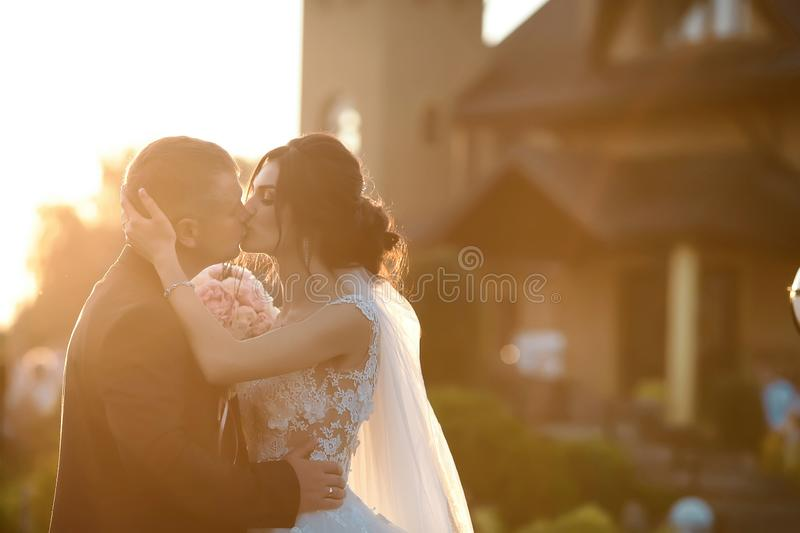 Stylish couple of happy newlyweds posing in the park on their wedding day. Gorgeous happy brunette bride in white dress kisses the stock image