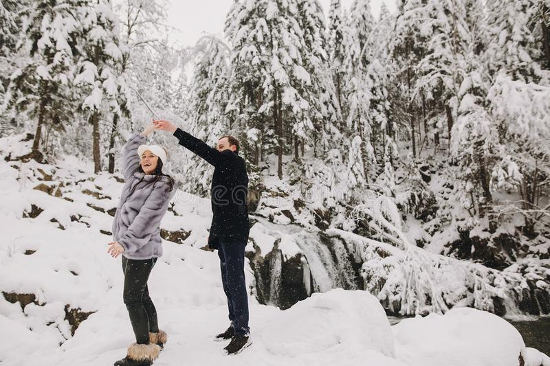 Stylish couple having fun in winter snowy mountains. Happy roman. Tic men and women in luxury clothes smiling and playing at waterfall in snow. Holiday getaway stock photo
