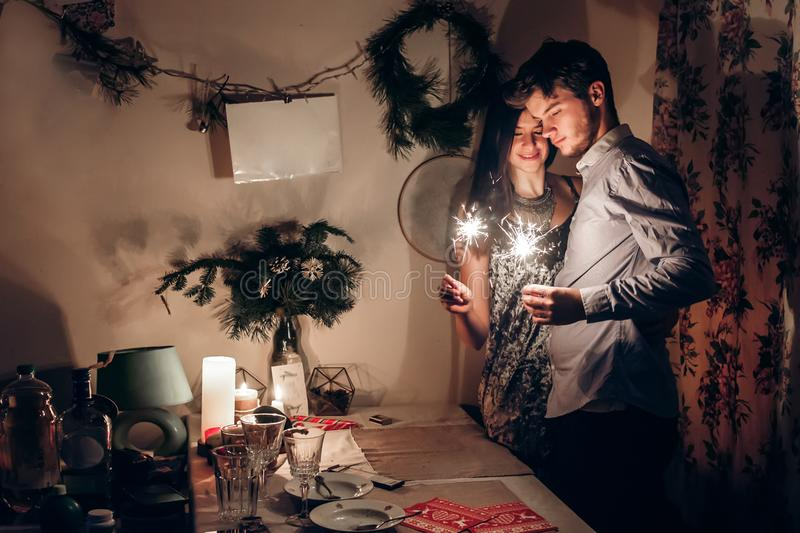 stylish couple holding burning sparkler bengal light and celebrating new year eve at home. merry christmas concept. happy family royalty free stock image