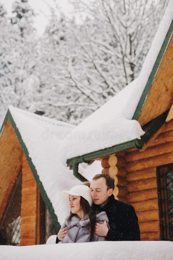 Stylish couple hugging in wooden cabin on background snowy woods stock images