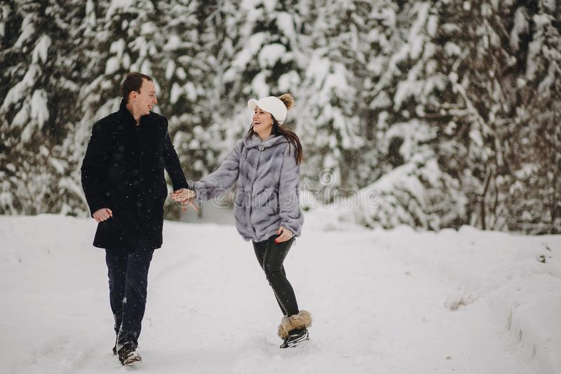 Stylish couple in love having fun in snowy mountains. Happy family playing in snow and smiling in winter mountains and forest. Ho royalty free stock photo