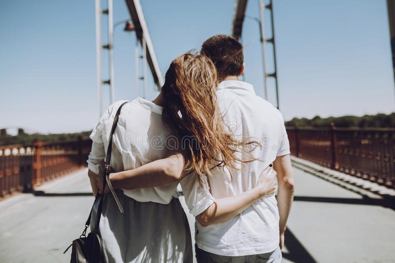 Stylish couple in love hugging, back view with windy hair, on br. Idge in the summer city. modern women and men in fashionable white clothes embracing at the stock photos