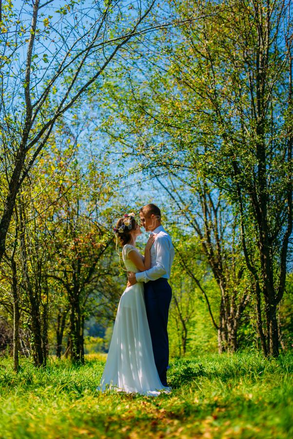 Stylish couple in love portrait, Newlywed husband and wife in circlet of flowers hugging near tree outdoors, summer nature concept stock image