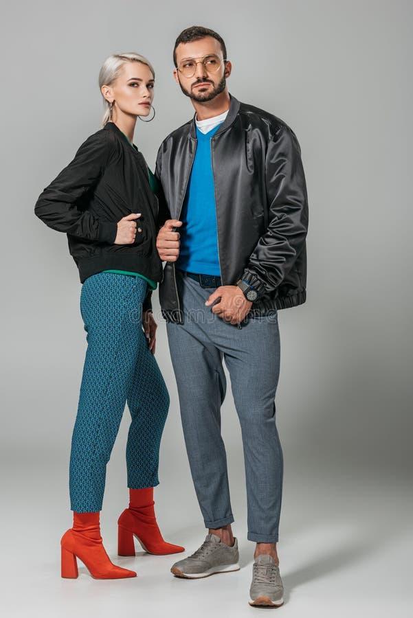 stylish couple of models posing in black jackets on grey stock photography