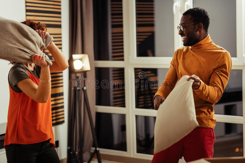 Stylish couple wearing bright clothes having pillow battle. Bright clothes. Stylish couple wearing fashionable bright clothes having pillow battle royalty free stock images