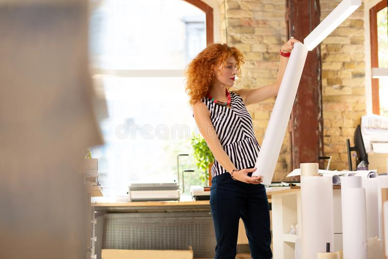 Stylish curly woman wearing striped blouse holding roll of paper stock image