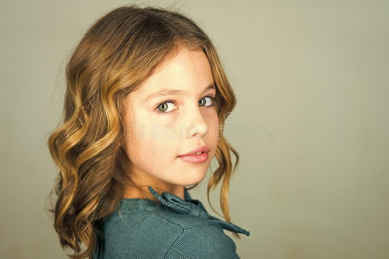 Stylish cute kid posing on grey background. Face kid for magazine cover. Girl kids face portrait in your advertisnent. royalty free stock image