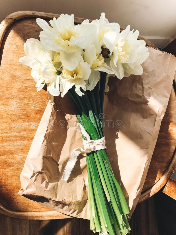 Stylish daffodils on rustic wooden chair in sunny light. Fresh yellow flowers bouquet on chair, countryside still life. Hello stock photo